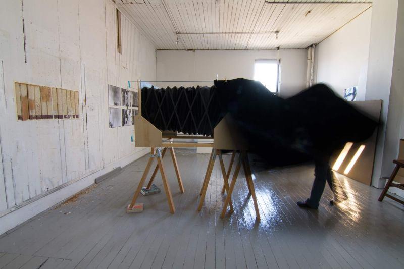 Installation view showing Trudi Lynn Smith under darkcloth of 16x20 camera